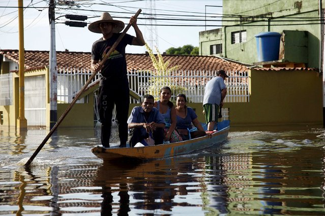 People sit in a boat in a flooded street in Guasdualito, in the state of Apure, Venezuela, July 4, 2015. (Photo by Carlos Eduardo Ramirez/Reuters)