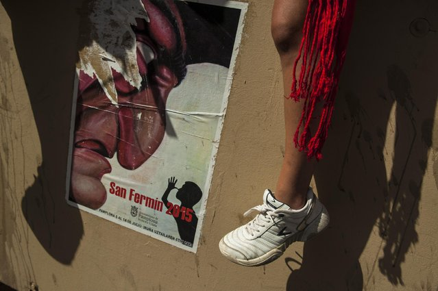 """A reveler wearing white and red sits beside an official poster for the San Fermin Fiestas during the launch of the """"Chupinazo"""" rocket, to celebrate the official opening of the 2015 San Fermin Fiestas, in Pamplona, northern Spain, Monday, July 6, 2015. (Photo by Alvaro Barrientos/AP Photo)"""