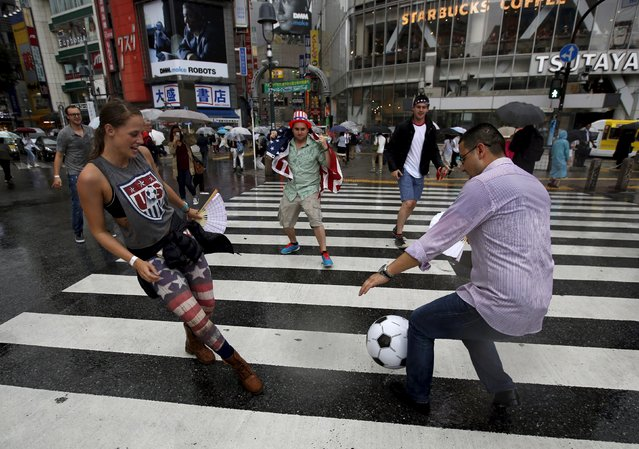 U.S. residents in Japan kick a ball as they celebrate their country's victory after their Women's World Cup final soccer match against Japan in Vancouver, on a diagonal crossing at Tokyo's Shibuya shopping and amusement district, Japan, July 6, 2015. (Photo by Issei Kato/Reuters)