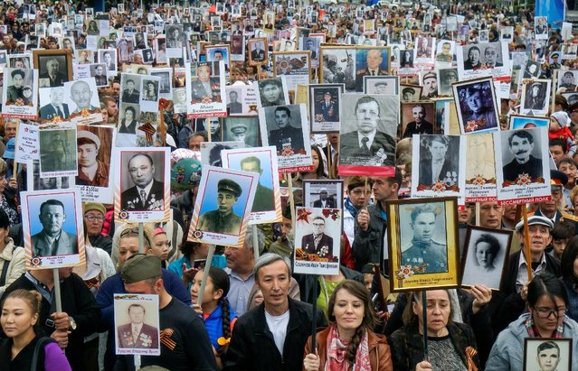 People carrying portraits of deceased relatives who took part in World War Two, march in a parade during Victory Day commemorations in  Almaty, Kazakhstan, May 9, 2016. (Photo by Shamil Zhumatov/Reuters)
