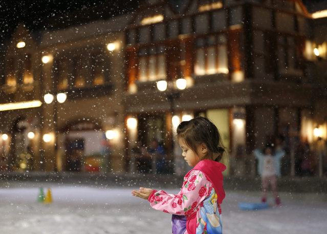 A photo made available on 08 July 2015 shows a little Thai girl enjoying artificial snow at Snow Town park in Bangkok, Thailand, 07 July 2015. Amid the heat, humidity and high temperatures of Bangkok, the newly opened Snow Town themed park attracts local and foreign tourists to escape from the hot weather and to experience the cold climate with snow activities like snow sledding and snowball fighting. (Photo by Rungroj Yongrit/EPA)