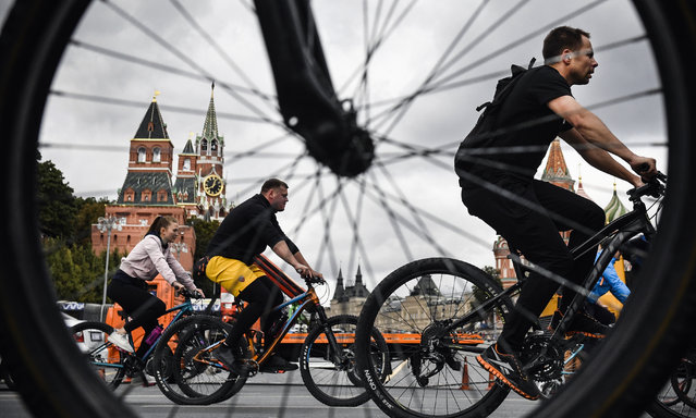 People ride their bike past the Red Square as they attend a bicycle festival in central Moscow on September 15, 2019. (Photo by Alexander Nemenov/AFP Photo)