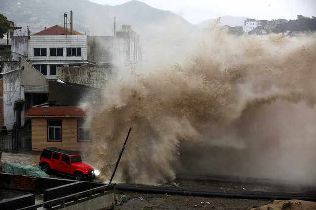 A strong wave breaks over a vehicle along the shore ahead of the landfall of Typhoon Chan-Hom in Wenling in eastern China's Zhejiang province Friday July 10, 2015. Chinese authorities have evacuated tens of thousands of people, canceled scores of trains and flights and shuttered seaside resorts as a super-typhoon with wind gusts up to 200 kilometers per hour (125 mph) heads toward the southeastern coast. (Photo by Chinatopix via AP Photo)