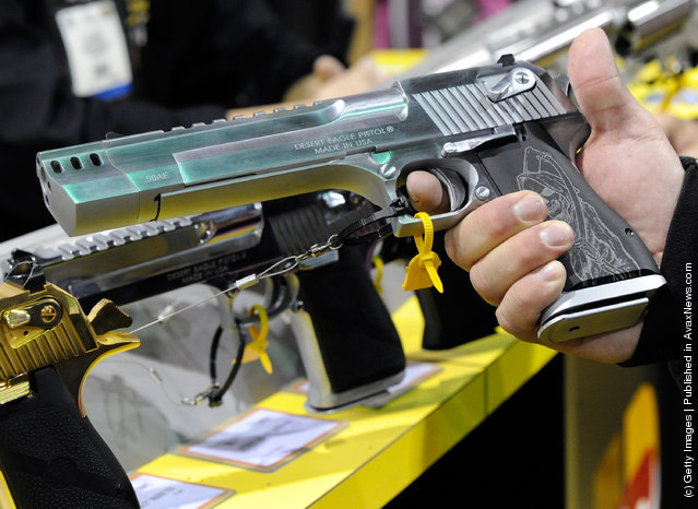 An attendee holds a .50 Action Express (.50 AE) Desert Eagle semi-automatic pistol at the Kahr Arms booth