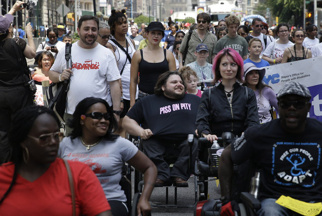 Matthew Clark, center, of Philadelphia, participates in the inaugural Disability Pride Parade in New York, Sunday, July 12, 2015. (Photo by Seth Wenig/AP Photo)