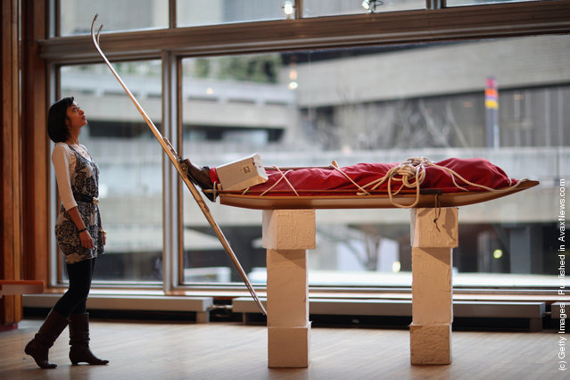 South Bank employee Lara Delaney stands besides a coffin in the shape of a skier