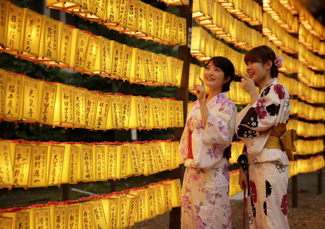 Two office workers wearing summer kimonos Yukata look at paper lanterns as they visit on the eve of Mitama Matsuri, a summer festival at Yasukuni Shrine in Tokyo, Japan, 13 July 2015. About 300,000 people visit the shrine decorated with about 30,000 lanterns during the three-day summer festival aiming at comforting souls of dead, especially for the war dead. The festival is after Japan's Buddhist custom to honor and comfort souls of family's ancestors. (Photo by Kimimasa Mayama/EPA)