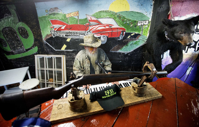 Eddie McDaniel, who goes by Fast Eddie, plays piano for visitors at Old Car City, the world's largest known classic car junkyard, Thursday, July 16, 2015, in White, Ga. McDaniel and owner Walter Dean Lewis grew up playing in the cars on the lot which started as a general store selling auto parts in 1931 by Lewis' parents. (Photo by David Goldman/AP Photo)