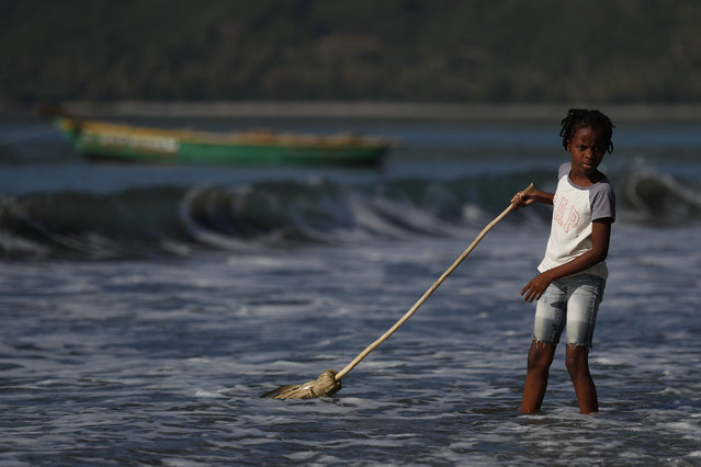 A girl washes a broom in the ocean in Jacmel, Haiti, Sunday, October 6, 2019. (Photo by Rebecca Blackwell/AP Photo)