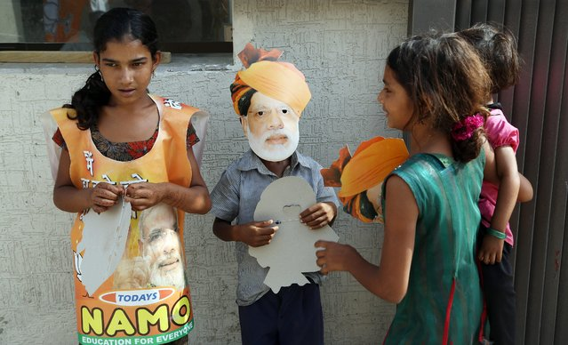 A child wears a mask of Bharatiya Janata Party's prime ministerial candidate Narendra Modi at the BJP's state headquarters in Gandhinagar, on May 16, 2014. (Photo by Divyakant Solanki/EPA)