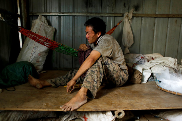A banana plantation worker cries as he sits inside his shack during a day off at a plantation operated by a Chinese company in the province of Bokeo in Laos April 26, 2017. (Photo by Jorge Silva/Reuters)
