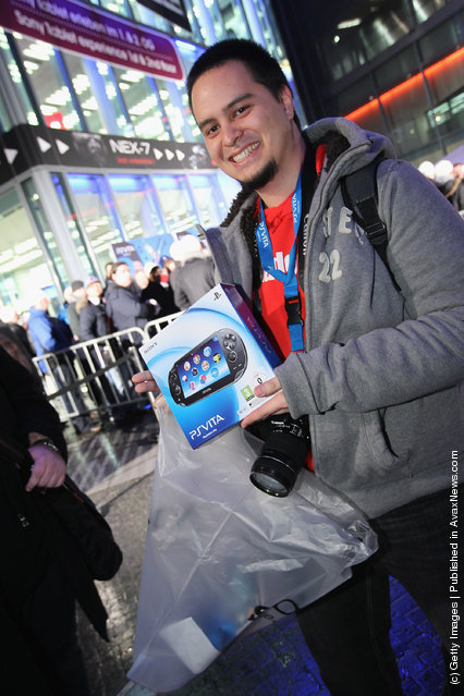 A young man shows off his new Sony PlayStation Vita portable gaming device that he just bought at the Sony Store during the official German launch of the new Vita