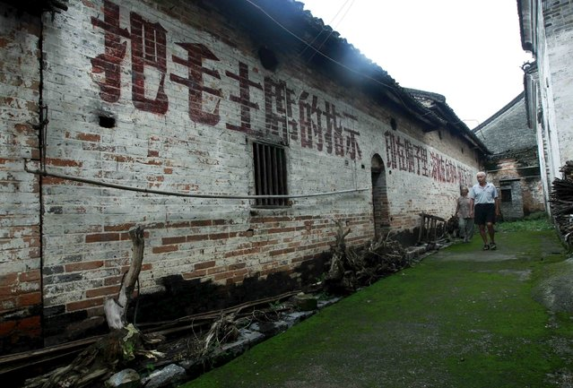 """Villagers walk past a house where revolutionary slogans are painted on the wall in Dongzhai village, Guangxi Zhuang Autonomous Region, China, July 19, 2015. The village, with a population about 1,600 people, is known locally for its revolutionary slogans dating from the 1950s, which could be seen on almost every old house, local media reported. The slogan on the wall reads: """"Take Chairman Mao's instructions, mark them in the brain, melt them in the blood and practice them in action"""". (Photo by Reuters/Stringer)"""