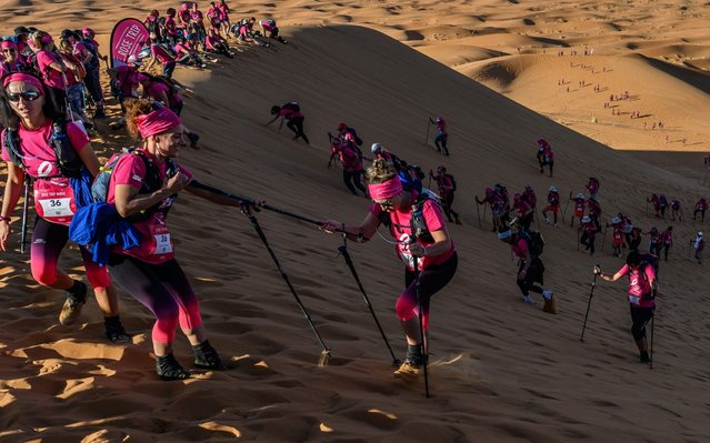 """Women clumb up a sand dune as they take part in the desert trek """"Rose Trip Maroc"""", on November 4, 2019 in the erg Chebbi near Merzouga. The Rose Trip Maroc is a female-oriented trek where teams of three must travel through the southern Moroccan Sahara desert with a compass, a map and a topographical reporter. (Photo by Jean-Philippe Ksiazek/AFP Photo)"""
