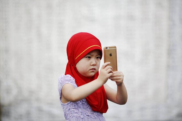 A girl takes pictures at the historic Niujie mosque as Muslim believers gather to celebrate the Eid al-Fitr in Beijing July 18, 2015. (Photo by Damir Sagolj/Reuters)