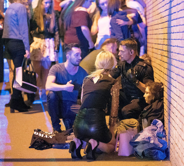 Police and other emergency services are seen near the Manchester Arena after reports of an explosion. Police have confirmed they are responding to an incident during an Ariana Grande concert at the venue. Reported Explosion at Manchester Arena, UK on May 22, 2017. (Photo by Rex Features via AP Images)