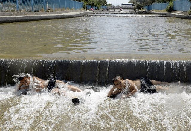 Children lie in a canal to cool off from summer heat in Urumqi, Xinjiang Uighur Autonomous Region, China, July 22, 2015. The highest temperature in the city reached 40 degrees Celsius (104 degrees Fahrenheit) on Wednesday, local media reported. (Photo by Reuters/Stringer)