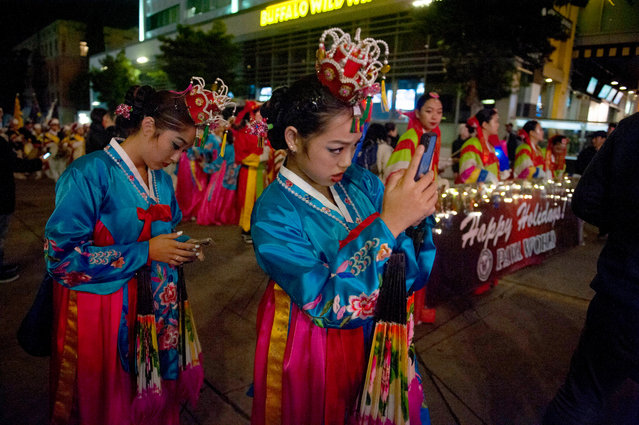 Participants wearing East Asian traditional costumes take photos during the 88th annual Hollywood Christmas Parade in Hollywood, Californi​a, USA, 01 December 2019. (Photo by Christian Monterrosa/EPA/EFE)
