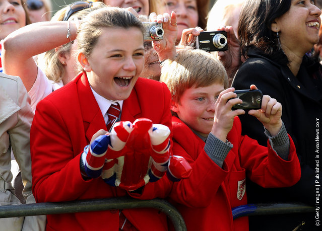School children take photographs as Queen Elizabeth II arrives in Valentine's Park Redbridge as part of her Diamond Jubilee tour of the UK