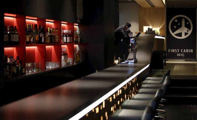 People stand at the front desk near a bar at First Cabin hotel, which was converted from an old office building, in Tokyo, July 3, 2015. (Photo by Toru Hanai/Reuters)