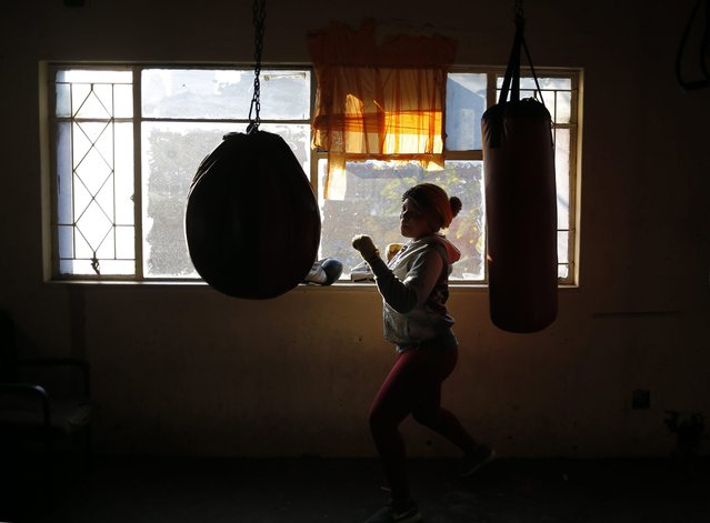 "A female boxer trains during an early morning training session at the inner city boxing gym in Hillbrow, Johannesburg, South Africa, 06 June 2016. Boxers from the inner city boxing gym trained in memorial to the late Muhammad Ali, dubbed as ""The Greatest"", who died on 03 June 2016 in Phoenix, Arizona, USA, at the age of 74. A public funeral procession and memorial service will be conducted 10 June 2016 in Louisville. (Photo by Kim Ludbrook/EPA)"
