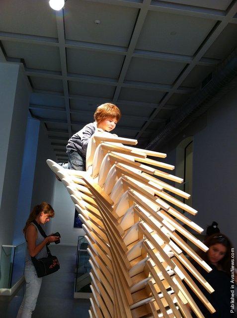Boy climbing chairs By Patricia Piccinini