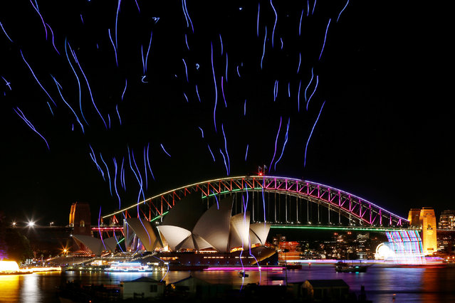 An aerial performance featuring 100 illuminated drones lift off from a barge on Sydney Harbour in front the Sydney Harbour Bridge and Opera House during the Vivid Sydney light festival in Sydney, Australia, June 9, 2016. (Photo by Jason Reed/Reuters)