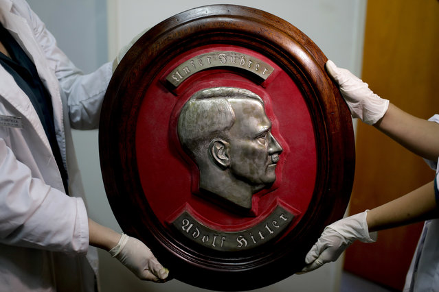 Members of the federal police show a bust relief portrait of Nazi leader Adolf Hitler at the Interpol headquarters in Buenos Aires, Argentina, Friday, June 16, 2017. In a hidden room in a house near Argentina's capital, police believe they have found the biggest collection of Nazi artifacts in the country's history, including a bust relief of Adolf Hitler, magnifying glasses inside elegant boxes with swastikas and even a macabre medical device used to measure head size. Some 75 objects were found in a collector's home in Beccar, a suburb north of Buenos Aires, and authorities say they suspect they are originals that belonged to high-ranking Nazis in Germany during World War II. (Photo by Natacha Pisarenko/AP Photo)