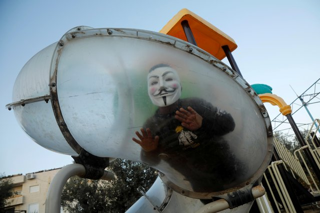 A Palestinian boy wearing a mask enjoys a ride in a park in Bethlehem in the Israeli-occupied West Bank on December 17, 2019. (Photo by Raneen Sawafta/Reuters)