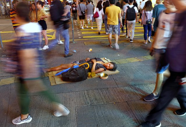 People rush past a man sleeping on the pavement on Argyle street at Mong Kok district in Hong Kong, September 7, 2019. (Photo by Kai Pfaffenbach/Reuters)