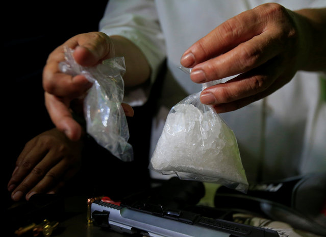 A bag of a methamphetamine, known as shabu, is shown by a National Bureau of Investigation agent after a raid on the home of a police officer and member of the anti-drugs unit in metro Manila, Philippines May 25, 2016. (Photo by Romeo Ranoco/Reuters)