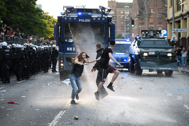 """Protestors are sprayed by police water cannons during the """"Welcome to Hell"""" anti-G20 protest march on July 6, 2017 in Hamburg, Germany. Leaders of the G20 group of nations are arriving in Hamburg today for the July 7-8 economic summit and authorities are bracing for large-scale and disruptive protest efforts. (Photo by Leon Neal/Getty Images)"""