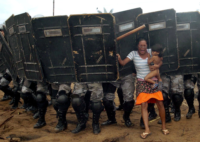 An indigenous woman holds her child while trying to resist the advance of Amazonas state policemen who were expelling the woman and some 200 other members of the Landless Movement from a privately-owned tract of land on the outskirts of Manaus, in the heart of the Brazilian Amazon March 11, 2008. The landless peasants tried in vain to resist the eviction with bows and arrows against police using tear gas and trained dogs. (Photo by Luiz Vasconcelos/Reuters)