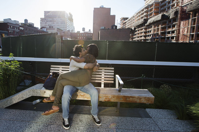 A couple kisses as they sit on a bench enjoying the sunshine on the High Line park in New York, June 12, 2013. (Photo by Lucas Jackson/Reuters)