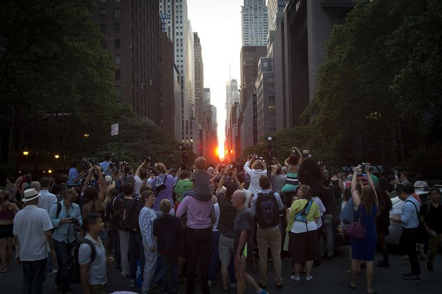 """People crowd a bridge that goes over 42nd Street as they take photos of the """"Manhattanhenge"""" phenomenon in the Manhattan borough of New York July 11, 2014. Manhattanhenge, coined by astrophysicist Neil deGrasse Tyson, occurs twice a year, when the setting sun aligns itself with the east-west grid of streets in Manhattan. (Photo by Carlo Allegri/Reuters)"""