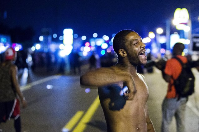 An anti-police demonstrator marches in protest in Ferguson, Missouri August 11, 2015. (Photo by Lucas Jackson/Reuters)