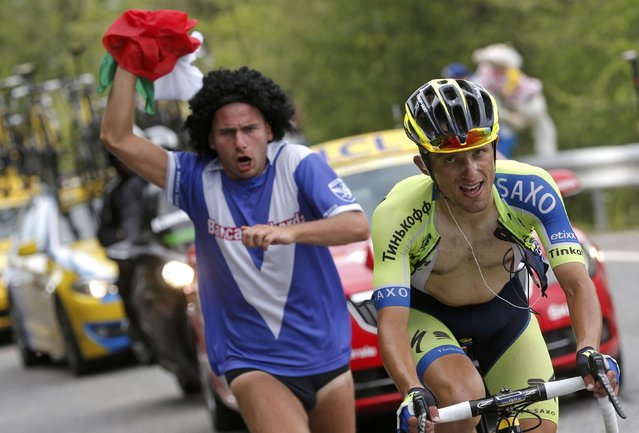 Tinkoff-Saxo team rider Ral Majka of Poland is chased by a supporter as he cycles to win the 177-km fourteenth stage of the Tour de France cycling race between Grenoble and Risoul, July 19, 2014. (Photo by Christian Hartmann/Reuters)