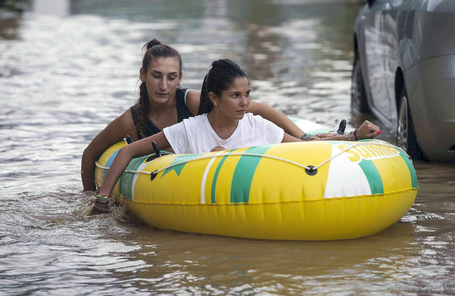 Two girls on a rubber boat paddle with their hands as they transit at a flooded street in Rossano, Calabria, Southern Italy, 12 August 2015. In the town of Rossano, near Cosenza, roads and homes were afected by floods as waters swept away cars and dumped them on the seafront. People in the affected areas have been evacuated. (Photo by Francesco Arena/EPA)
