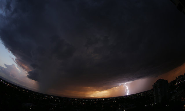 In this photo taken with a fisheye lens, a massive storm cloud packing high winds, hail and heavy rains sweeps over downtown Denver as lightning strikes on the horizon on Monday, July 7, 2014. After a daytime high that reached 100 degree, forecasters predict that heavy thunderstorms will envelop Colorado's Front Range communities through the night. (Photo by David Zalubowski/AP Photo)