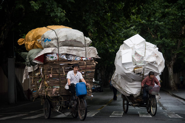 Waste collectors ride their loaded tricycles on the streets in Shanghai, China on June 20, 2016. (Photo by Johannes Eisele/AFP Photo)