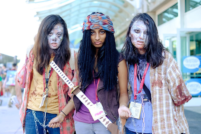 "Sirisha Verigonda, center, of San Diego, CA, poses as Michonne from the show ""The Walking Dead"" with two zombies, Emily Zheng, left, and Gina Huang, both of San Diego, during the 45th annual San Diego Comic-Con on July 24, 2014 in San Diego, California. (Photo by T. J. Kirkpatrick/Getty Images)"