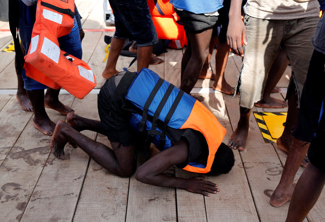 A migrant prays on his knees after boarding the Migrant Offshore Aid Station (MOAS) rescue ship Topaz Responder around 20 nautical miles off the coast of Libya, June 23, 2016. (Photo by Darrin Zammit Lupi/Reuters)