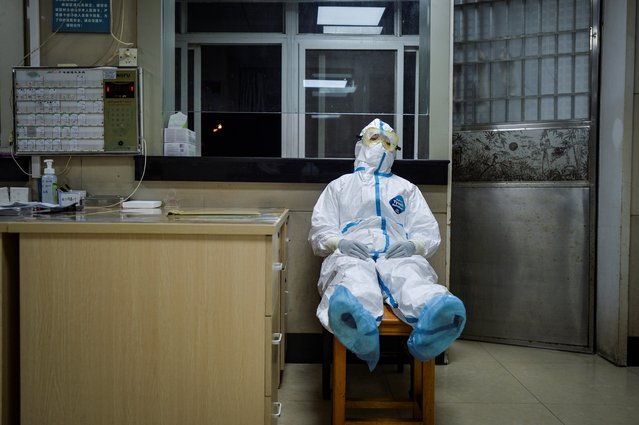 A medical worker in a protective suit takes a break during her night shift at a community health service center, which has an isolated section to receive patients with mild symptoms caused by the coronavirus and suspected patients, in Qingshan district of Wuhan, Hubei province, February 9, 2020. (Photo by Reuters/China Daily)