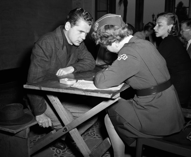 Among the estimated 3,000,000 youths between the ages of 18 and 20 who registered in the selective service enrollment was film actor Jackie Cooper,19, who was registered on June 30, 1942 at Beverly Hills, Calif., by Hetty Vorhaus, a member of the Woman's Emergency Corps. (Photo by Ira W.  Guldner/AP Photo)