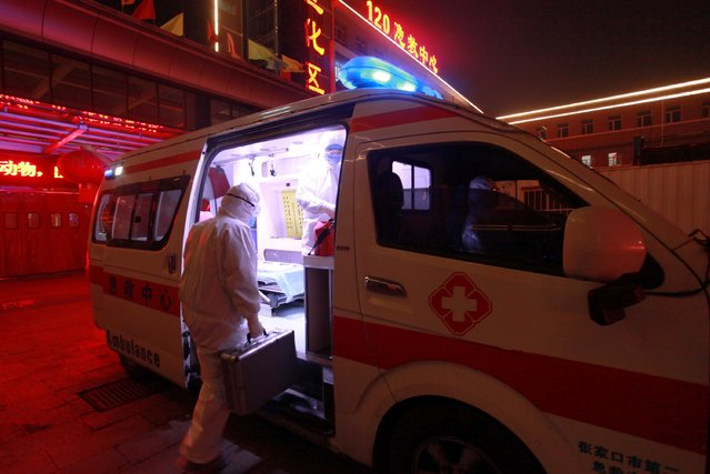 A medical worker in protective suit gets into an ambulance at a hospital in Xuanhua district of Zhangjiakou, Hebei province, China on February 13, 2020. (Photo by Reuters/China Daily)