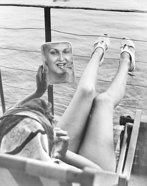 1949: Feet up on the rails, a woman studies her reflection in a mirror whilst sunbathing on the deck of a yacht in Portofino, Italy