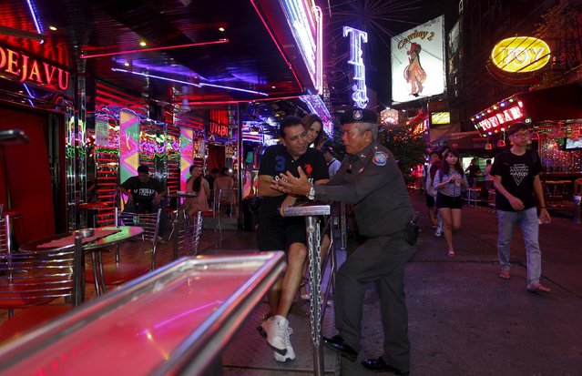 A police officer on patrol speaks with tourist at a bar in central Bangkok, Thailand, August 19, 2015. (Photo by Kerek Wongsa/Reuters)