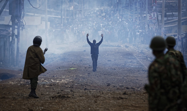 A man seeking safety walks with his hands in the air through a thick cloud of tear gas towards riot police, as they clash with protesters throwing rocks in the Kawangware slum of Nairobi, Kenya Thursday, August 10, 2017. International observers on Thursday urged Kenyans to be patient as they awaited final election results following opposition allegations of vote-rigging, but clashes between police and protesters again erupted in Nairobi. (Photo by Ben Curtis/AP Photo)