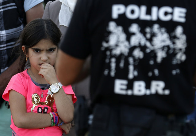 A migrant girl looks as police officers secure the railway tracks before a train that would take the migrants towards Serbia enters the railway station, in the southern Macedonian town of Gevgelija, Wednesday, August 20, 2015. (Photo by Darko Vojinovic/AP Photo)