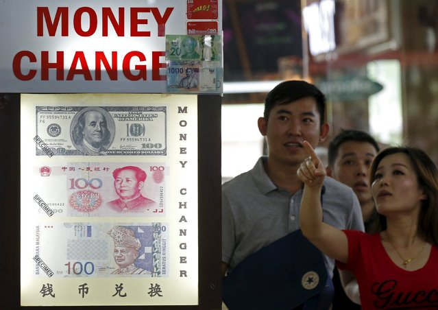 People look at the exchange rate at a moneychanger displaying a poster of U.S. dollar bill, Chinese Yuan and Malaysia Ringgit in Singapore August 24, 2015. The Malaysian ringgit hit a fresh pre-peg 17-year low on Monday as sustained worries about China's economy dented global risk appetite with European and Wall Street stocks suffering their largest one-day drop in nearly four years. (Photo by Edgar Su/Reuters)